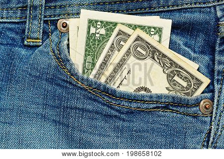 Old shabby one US dollar bank notes in worn work jeans pocket - poverty symbol and financial crisis concept