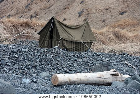 Canvas tent on the rocky shore. A small tent after the wind on the shore of the sea of Okhotsk far East Russia.