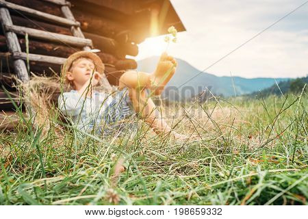 Little boy rest in green grass near the hayloft in garden