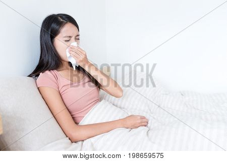 Sick Woman sneezing on bed