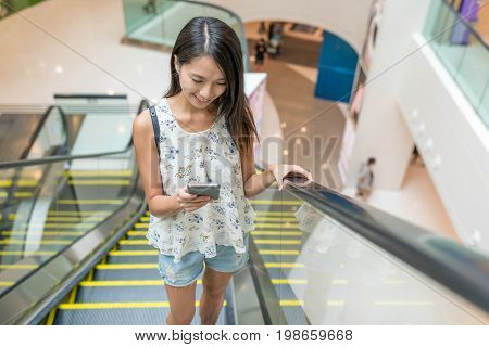 Woman taking escalator and using cellphone