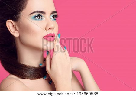 Beauty makeup. Fashion women closeup portrait. Blue manicured nails. Glamour young brunette with eye shadow visage and matte lipstick isolated over pink background.