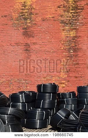Coiled plastic pipes stored outdoors Near the old red brick wall
