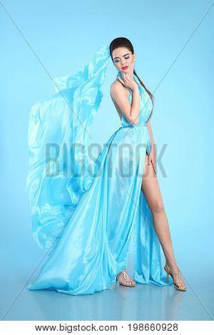 Beautiful High Fashion model in blue blowing chiffon dress. Glamour stunning Woman in long flying silk fabric waving on wind evening dress.