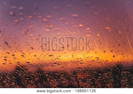 raindrops on car windshield on red sunset with bulred car lights on background
