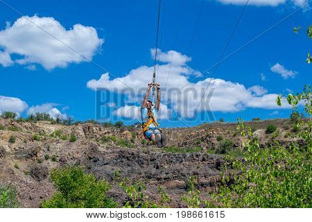 Ukraine Migea - July 30 2017: Zipline. The men in the equipment slides on a steel cable. Trolley Track Over the lake. Extreme and active rest.