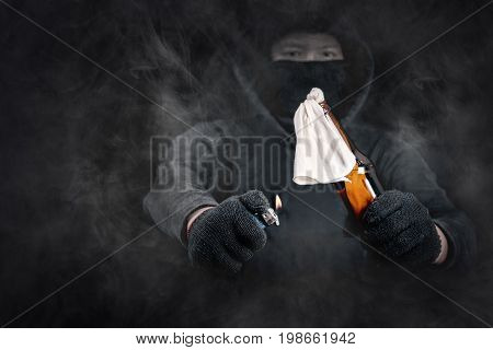 Protester or terrorist with Molotov cocktail as known as petrol bomb or bottle bomb with smoke dramatic screen