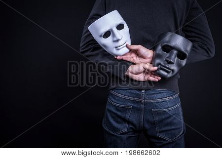 Mystery man holding black and white mask. Anonymous social masking concept.
