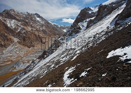Hunter goes on the trail on a mountain in the Tien Shan. Kyrgyzstan. Rocks stones snow autumn hunting