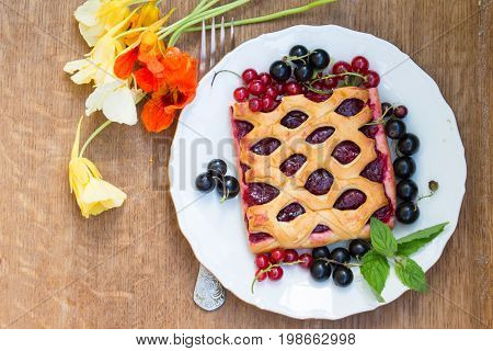 Cake With Berry Jam Is Served With Fresh  Red And Black Currant On A Wooden Table. Garden Flowers Na