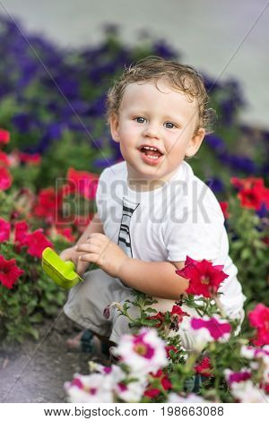 Funny little boy sitting with toy shovel on flower bed on warm sunny day. Environment concept.