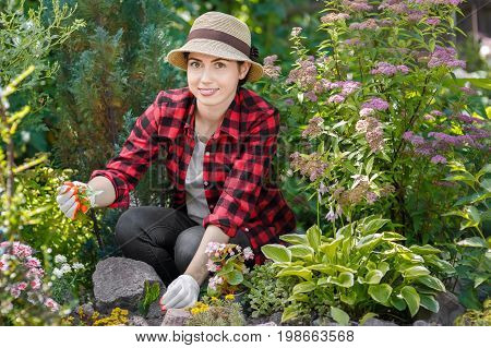 young woman gardener care of flowers in the garden. Girl pulling out the weeds in flowerbed. People, gardening, care of flowers, hobby concept
