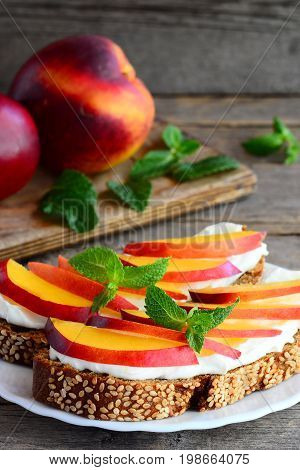 Delicious nectarine and cream cheese toast sandwiches. Homemade open sandwiches with cream cheese and fresh nectarine slices on a white plate and vintage wooden background. Vertical photo