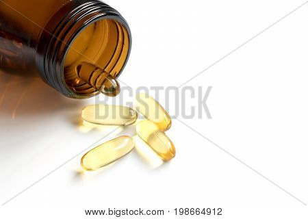 Yellow soft gelatin capsule with amber bottle on white background and have the copy space for add text