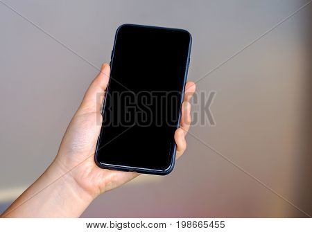 Woman holding a smart phone with blured background.