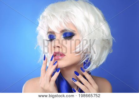 Blue makeup. Blonde bob hairstyle. Blond hair. Fashion Beauty Girl portrait. Sexy lips. Manicured nails and Make-up. Vogue Style Woman isolated on blue background.