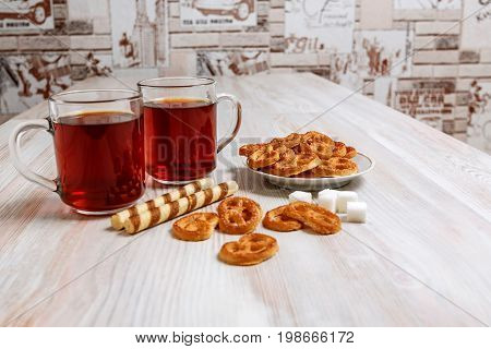 Two transparent cup of black tea on a light table and saucers with pretzels sweet sticks and pieces of refined sugar.