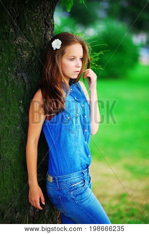 Portrait of a young pensive girl in the blue denim suit, leaning against the trunk of a tree in summer Park on a blurred background of green grass and bushes. Close-up