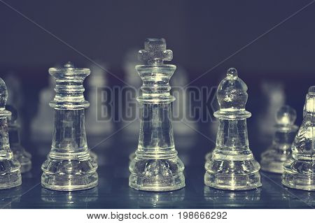 glass chess pieces is standing on board in dark
