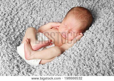 Newborn baby boy asleep on a grey blanket.
