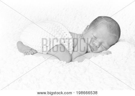 Newborn baby boy asleep on a white blanket.