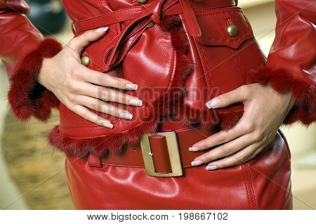 Body part of attractive woman in red leather jacket