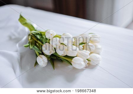 Bouquet Of Tulips On White Bed