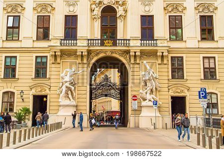 Vienna, Austria - April, 2, 2015: Arch and building view and tourists at Hofburg