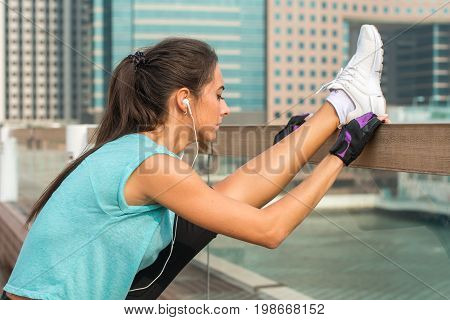Close up shot of young fitness woman working out on the city street doing exercises, stretching her legs, standing in a vertical split and listening to music in headphones