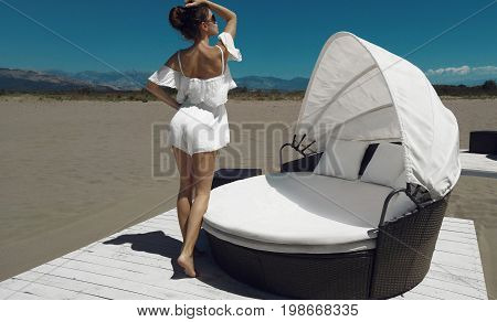 Fashionable glamour woman Luxury travel vacation. Fashion tanned brunette in white by beach sofa on sand before blue sky. Girl enjoying the sun carefree happy.