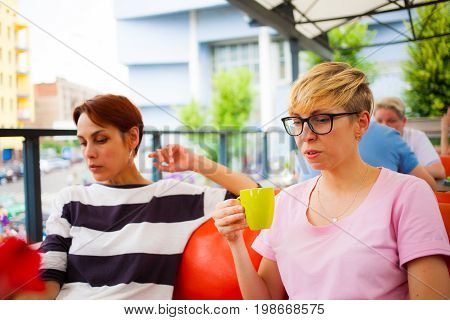 Girls Chat In A Cafe.