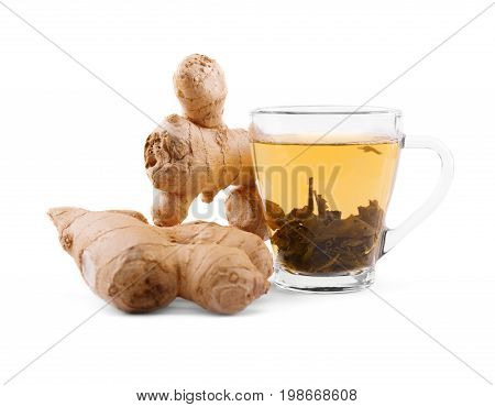 A close-up of a glass tea cup full of green tea isolated on a white background. A cup of yellow liquid and two big ginger roots. Winter organic beverage. Healthy tasty ginger tea.