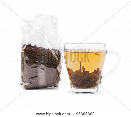 A transparent cup of traditional chinese green tea isolated on a white background. Hot, delicious and healthful black tea in a mug. A pack of dry and aromatic tea leaves. Herbal tea for a breakfast.