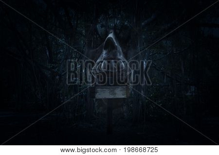 Cross with human skull scream over spooky forest at night time Horror background Halloween concept