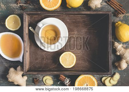 Ginger hot immunity boosting Vitamin natural drink With Lemon honey and cinnamon On tray and ingredients.