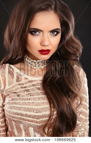 Beauty hair. Elegant fashion brunette woman portrait. Wavy hair style. Red lips Makeup. Healthy shiny hairstyle. Sexy girl model in sequin dress isolated on black background.