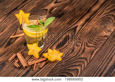A light and beautiful cup of hot green tea with cut lemon, exotic carambola and spicy cinnamon. Tasteful and natural black tea on a brown wooden background. Vegetarian beverages. Copy space.