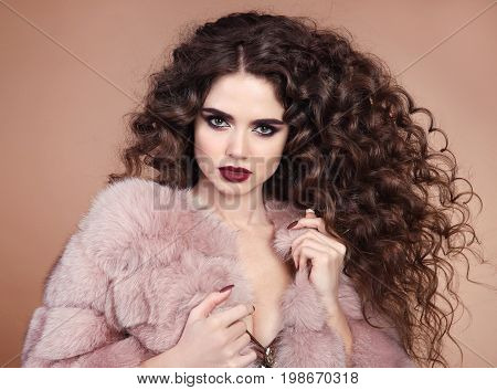 Healthy Beauty hair. Glamour portrait of beautiful brunette woman model with marsala matte lips makeup and long curly hairstyle in luxury fur coat isolated on beige background
