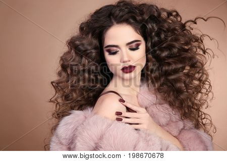 Hairstyle. Curly hair. Beauty makeup. Fashion brunette girl with long curly hair. Glamour portrait of beautiful brunette with marsala matte lips in pink fur coat isolated on beige background.