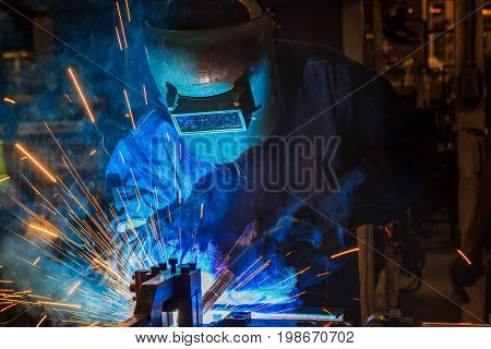 Industrial workers are welding assembly automotive part in car factory