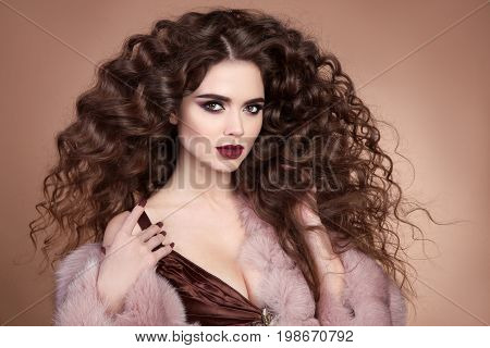 Beauty hair. Fashion brunette portrait of beautiful sexy woman model with marsala matte lips makeup and long curly hairstyle in luxury pink fur coat isolated on brown background