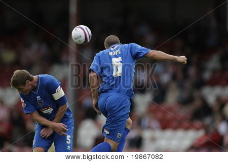 LONDON, UK AUGUST 16, Richard Hope heads the ball while Matt Heywood cowers away playing in the Coca-Cola football league two match between Brentford and Grimsby town at Griffin Park London August 16, 2008