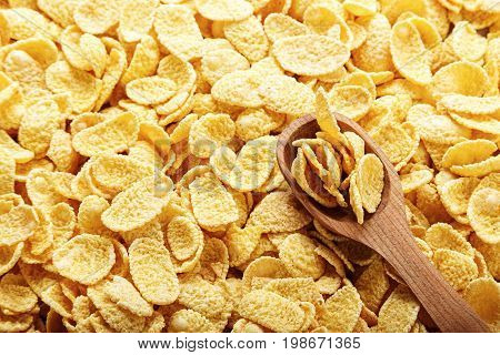 Cornflakes in brown scattered as a background in flakes a wooden spoon