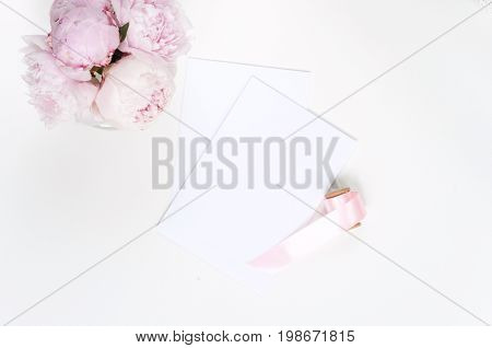 Woman modern background. Flat lay. Flower on the table. Keyboard and stapler. Home workplace. Table view. Business accessories. Mock-up background. Peonies. Glamour style.