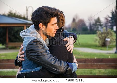Portrait of cheerful and handsome man hugging his best friend and looking away outdoor