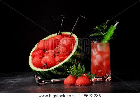 A colorful composition of a big cut watermelon with red honeydew and black straws, a tall glass of cold berry drink with ice and green peppermint and a metal scoop on a black table background.