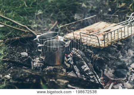 top view on bonfire with chicken meat and cup with water