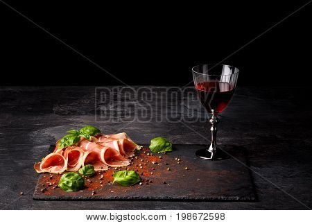 Close-up of fantastic sliced prosciutto and a glass of red wine on a black background. Appetizing traditional  wine with meaty restaurant snacks and basil leaves. Delicatessen concept. Copy space.