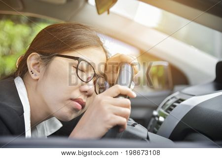 Tired Asian Business woman sleeping while driving a car. Illness exhausted disease for overtime working concept.