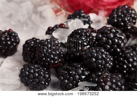 A close-up of ripe, cold, fresh, juicy blackberries on a frozen white table background. Crushed ice and purple blackberries full of vitamins. Rustic ingredients for homemade refreshing cocktails.